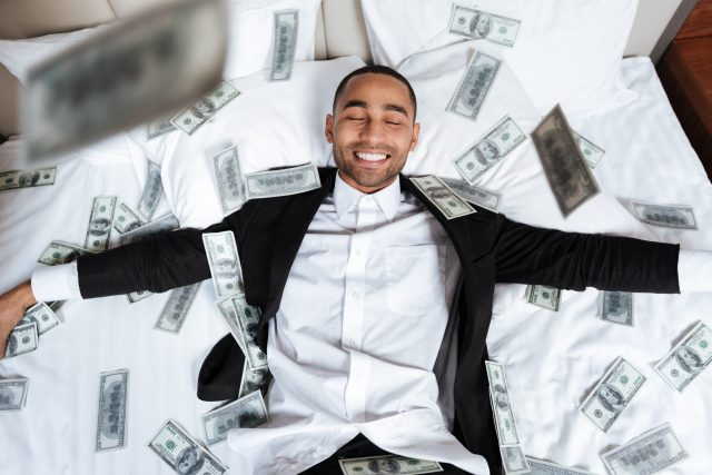 African man lying on bed with falling money